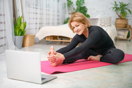 Fitness training online, senior woman at home with laptop
