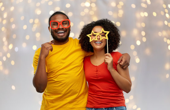 holidays, photo booth and people concept - happy african american couple with party props hugging over festive lights background