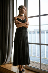 Portrait of a sad young woman with short hair standing looking out the window in a black dress