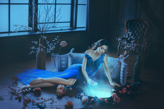 Fantasy young sorceress woman in long blue dress touch divine old mirror. Predictor future fairy tale Snow White. magic power of wind light spell. Mystic gothic art photo in dark black medieval room