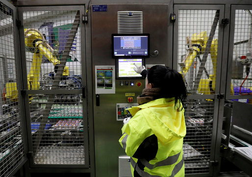 A worker operates robotic arms sorting yogurts at a distribution centre near Prague