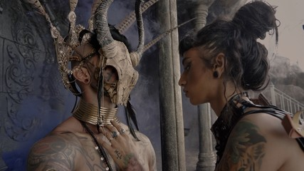Adventure scene.Girl in a tomb raider style with sword near Tattooed masked skull ethnic pagan shaman at ancient temple