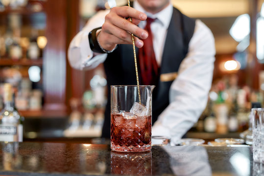Excellent skills. Cropped shot of young bartender standing at counter and mixing ingredients while making iced cocktail in the bar