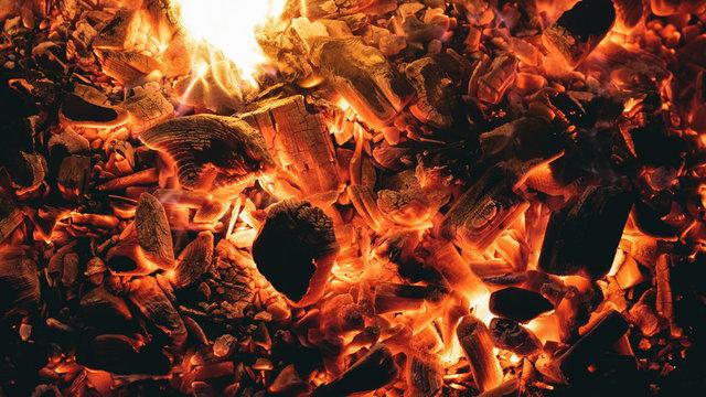 Burning coals close up texture background.
