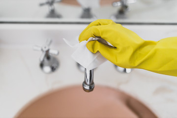 disinfecting surfaces from bacteria or viruses sill-life, hand with glove cleaning bathroom sink with disinfectant wet wipe