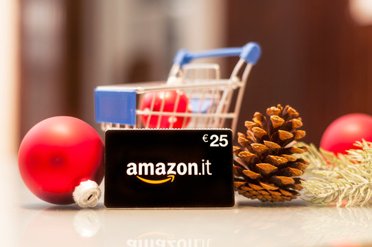 A 25 euro Amazon gift card on a glass table with a shopping cart and some Christmas decorations. The gift card allows you to shop online at the Amazon website