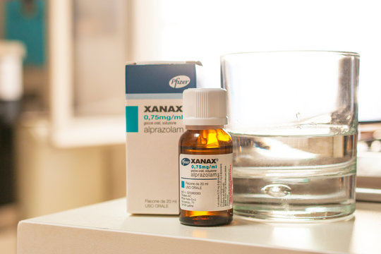 A bottle of Xanax drops with its box and a glass of water. It is commonly used in short term management of anxiety disorders.