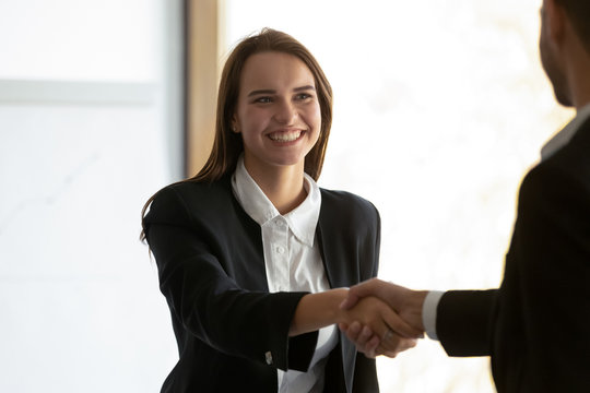 Head shot happy young female employee shaking hands with colleague. Millennial office worker getting reward or promotion. Smiling businesswoman welcoming client or making deal with new partner.