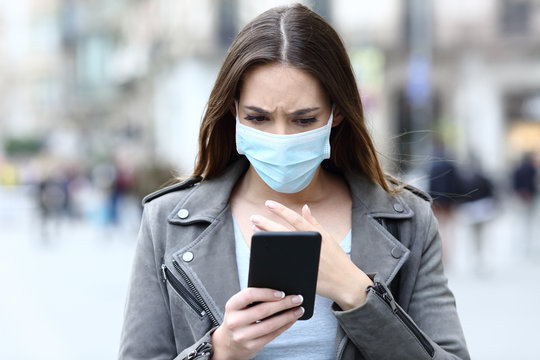Scared girl with mask reading news on her phone on street