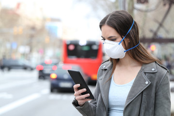 Woman with mask using phone with city traffic background Fotomurales