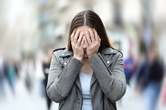 Woman suffering anxiety attack on city street