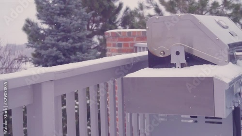 Wall mural Outdoor grill covered with snow on residential back patio in the Winter.