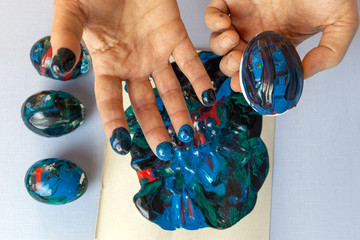 Woman's hands are painting eggs for easter with glowing colours. Decorating eggs with trendy blue colours and abstract paints