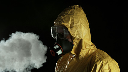Man in chemical suit with respirator and goggles.