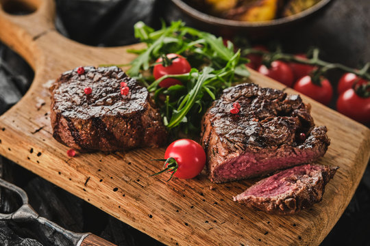 Grilled fillet steaks on wooden cutting board. Succulent thick juicy portions of grilled fillet steak served with tomatoes and roast potatoes on an old wooden board.