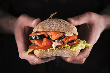 Papiers peints Snack Man's hands holding a sandwich with salmon, cucumber, tomatoes and mayonnaise sauce.