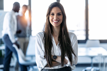 Smiling young businesswoman looking at camera while standing in the coworking space.