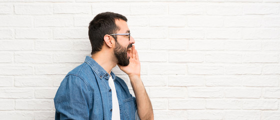 Handsome man with beard over white brick wall shouting with mouth wide open to the lateral