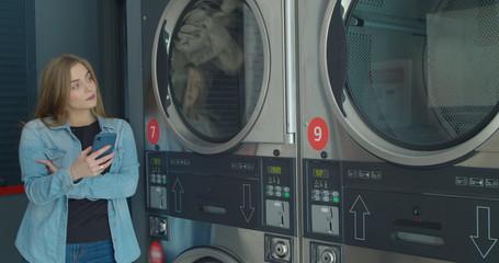Woman using smartphone while washing her laundry at laundromat.