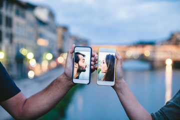 Young loving couple kissing virtually with the smart phone in front of Ponte Vecchio in Florence - Photo of millennials in two phones