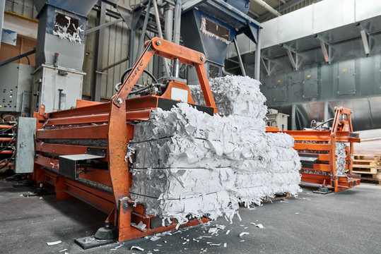 A paper recycling factory plant shredding machine, shredding waste paper into square bails, ready to be pulped and reused. Recycle waste materials to offset pollution and save the planet.