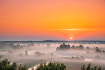 Fotorollo Koralle Amazing Sunrise Sunset Over Misty Landscape. Scenic View Of Foggy Morning Sky With Rising Sun Above Misty Forest And River. Early Summer Nature Of Eastern Europe