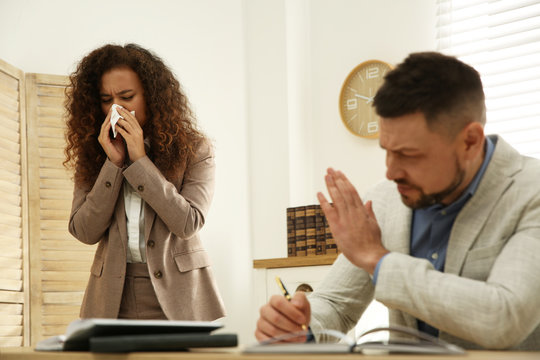 Sick African-American woman sneezing during meeting in office. Influenza virus