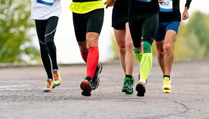 Fotomurales - legs male runners in compression socks and kinesio tape run marathon