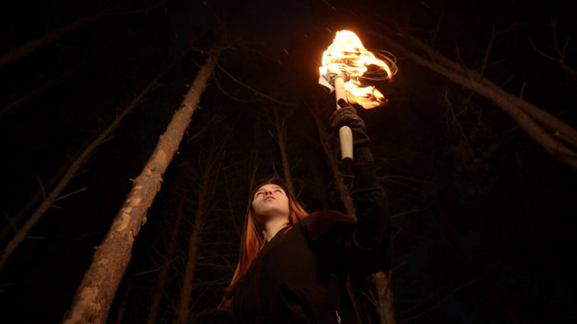 Young lost woman standing in scary winter forest at night with a handmade torch