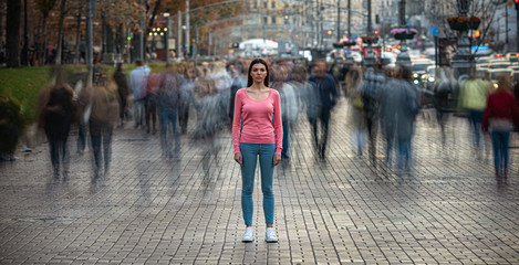 The young girl stands on the crowded urban street Fotomurales