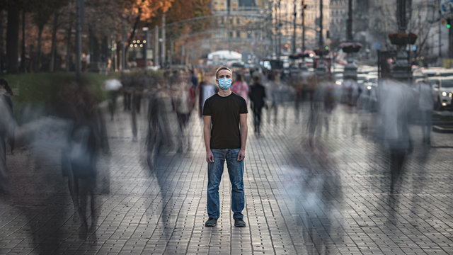 The young man with medical face mask stands on the crowded street