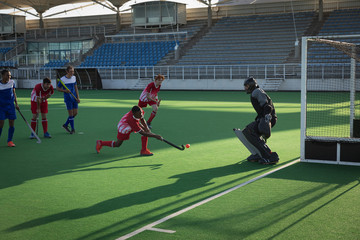 Field hockey player taking a shot a goal during a match
