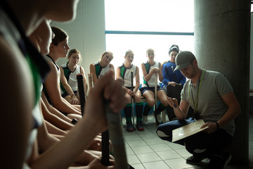 Female hockey players preparing match on a cloakroom