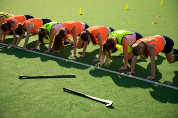 Female hockey players exercising on the field