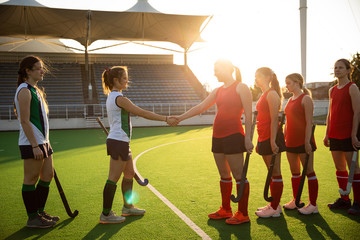 Female hockey players shaking hands before match