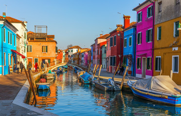 Beautiful view of the canals of Burano with boats and beautiful, colorful buildings. Burano village is famous for its colorful houses. Venice, Italy.