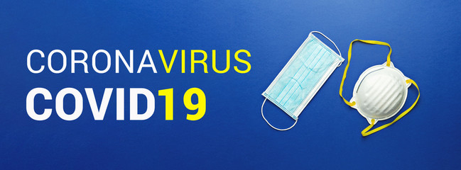 Two types of protective face masks on blue background with inscription CORONAVIRUS COVID-19. Protective masks as precaution in spread of coronavirus Covid-19 around world, banner, flat lay