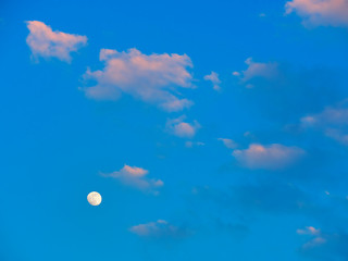 Glowing moon on blue sky with clouds background