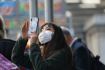 A woman wears a surgical mask while photographing the New York Stock Exchange