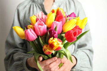 Woman holding beautiful spring tulips on white background, closeup