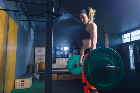 mulher levantando peso na academia estilo Cross