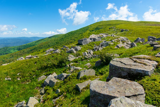 rocks on the alpine hillside meadow. beautiful summer nature scenery. green grass on the hills and fluffy clouds on the blue sky. wonderful mountain landscape of carpathians
