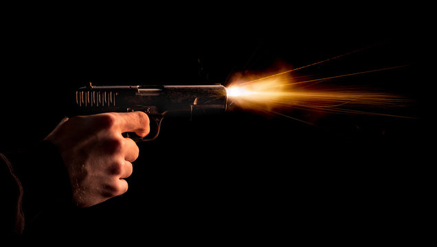 The hand presses the trigger of the gun and the flame from the shot escapes from its muzzle