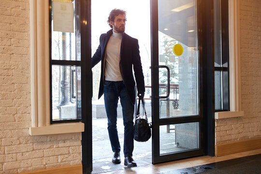 young businessman holding a black leather bag and opening the door of the office, full length photo. strange man thinking about robbery