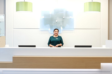 attractive woman manager is ready to serve you, welcome to the hostel, clinic, beauty center , close up photo. woman in green dress looking at the camera , lifestyle
