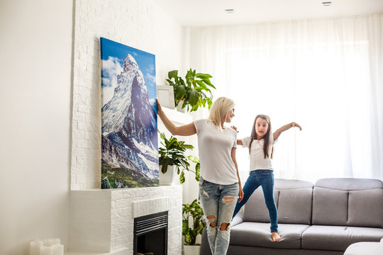 woman hangs photo canvas on wall