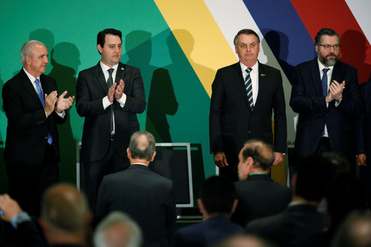 Attendees aplaude Brazilian President Jair Bolsonaro after his speech during the Brazil-USA Business Relations Seminar, in Miami