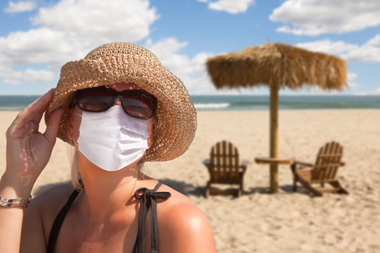 Vacationing Woman Wearing Face Mask on Sandy Beach.