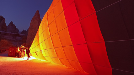 Foto auf Leinwand Ballon Hot air balloons preparing to fly at early morning in winter season in Cappadocia, Turkey