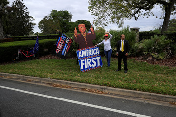 Supporters of U.S. President Donald Trump displays signs as the presidential motorcade passes by following a private fundraiser, in Longwood